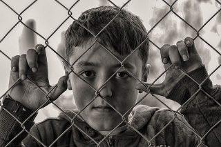Imagen de niño tras una malla metálica