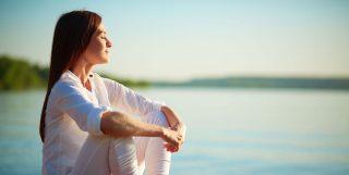 Mujer relajada y serena frente a lago