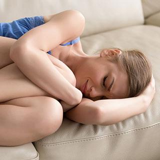 Mujer abatida en sofá con transtorno emocional